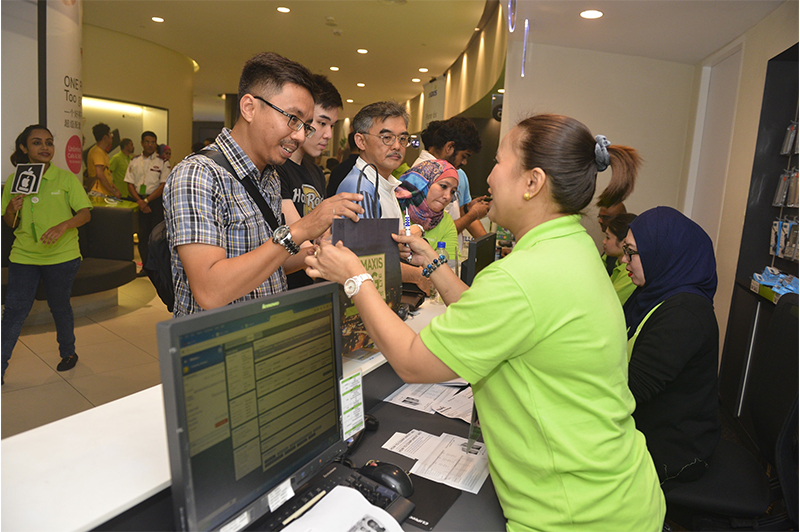 Mohd Nazrul Abdul Muttalib (left) was the first Maxis customer to collect his iPhone 6s Plus at the KLCC Maxis Centre at midnight.