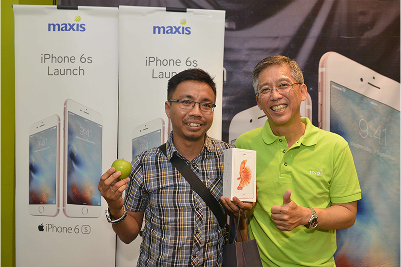 Mohd Nazrul, the first Maxis customer to collect his phone (left) with Tan Lay Han, Maxis' Head of Sales & Services (right) during the iPhone 6s launch at the KLCC Maxis Centre.